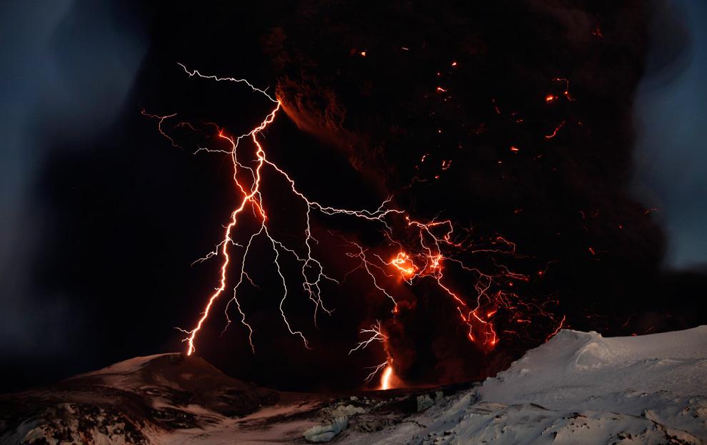 Лава извергается из вулкана Эйяфьятлайокудль на фоне молнии 17 апреля.