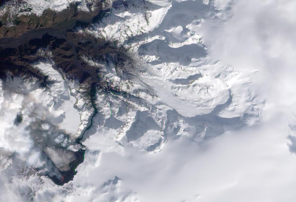 снимок естественного цвета, сделанном со спутника, видны фонтаны и потоки лавы, вулканический шлейф и пар от испаряющегося снега