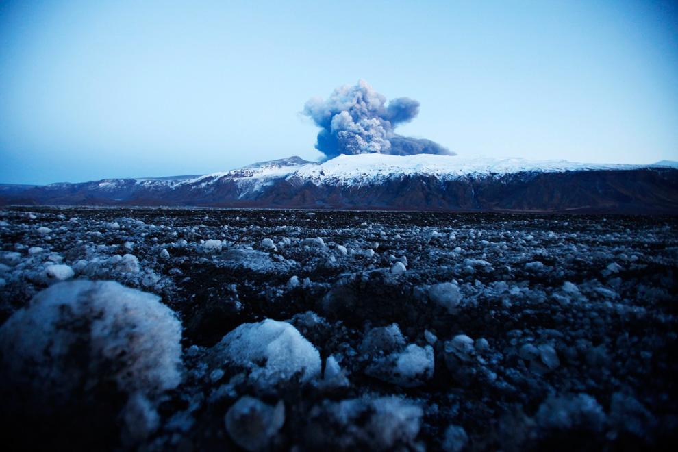 Куски льда от ледника лежат на фоне извергающегося вулкана недалеко от Эйяфьятлайокудля