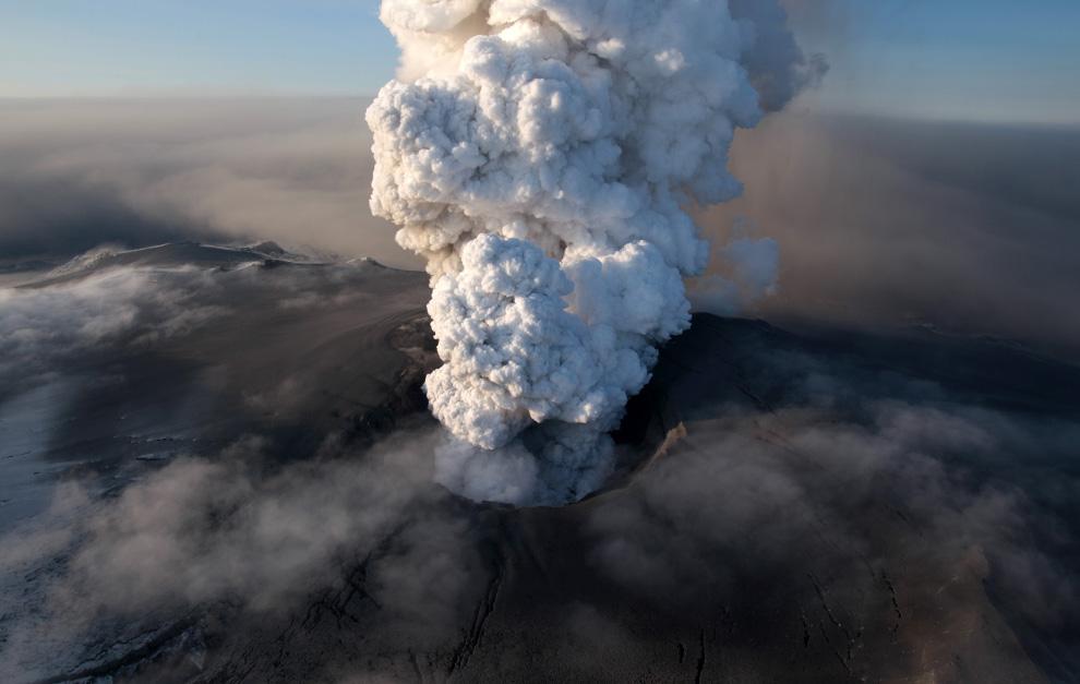 Пепел и столб пыли и грязи вырывается из кратера вулкана Эйяфьятлайокудль
