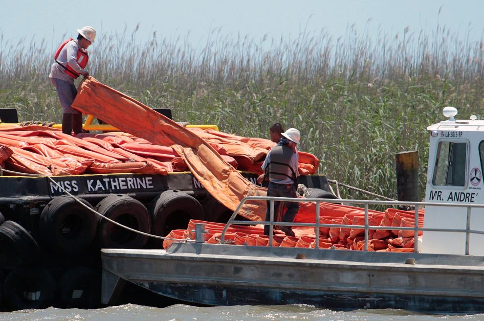 Рабочие грузят боновые заграждения на менее габаритное судно на реке Мисисиппи в Порт Идс 29 апреля. Различные инстанции прилагают огромные усилия, чтобы сдержать распространение нефти в моря и океаны.
