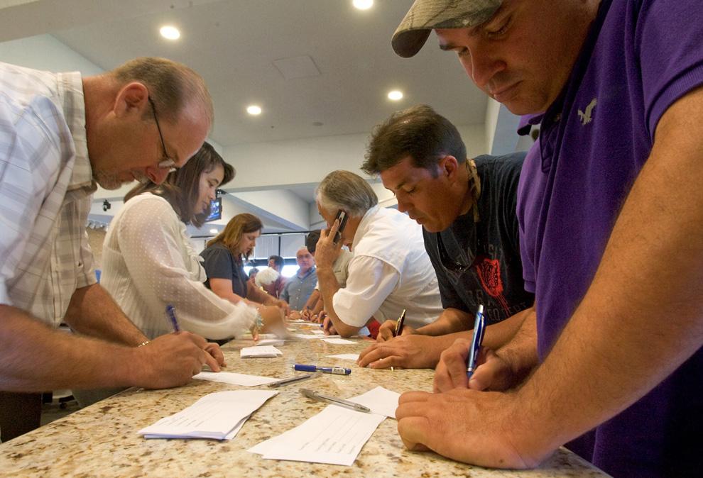 Рыбаки Луизианы подписывают формы, по которым они одалживают свои лодки и катера, чтобы помочь защитить прибрежные воды города Чалметте, штат Луизиана. Рыбаки организовали экстренное собрание, чтобы понять, как они могут использовать доступные ресурсы, чтобы помочь предотвратить утечку нефти в Мексиканский залив.